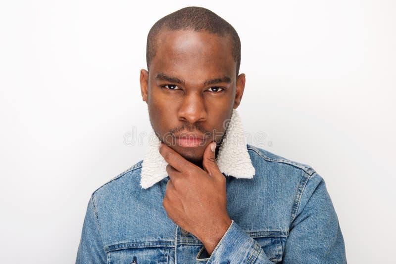 Fim acima do homem afro-americano novo fresco no revestimento da sarja de Nimes que pensa a mão de Wirth no queixo fotografia de stock royalty free