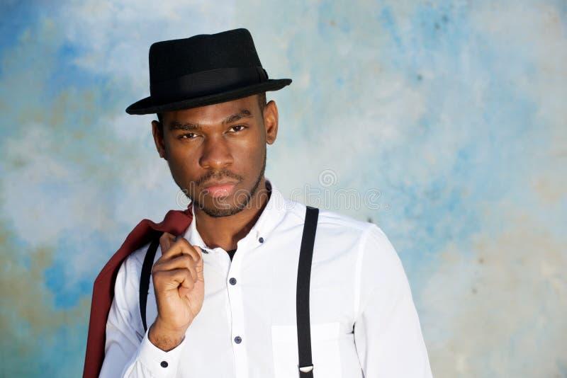Fim acima do homem afro-americano novo fresco que levanta com o chapéu contra a parede fotografia de stock royalty free