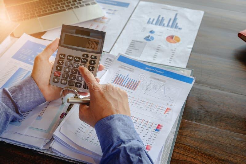 Fim acima do homem de negócios que usa a calculadora e o portátil para para fazer a finança da matemática na mesa de madeira no e imagens de stock royalty free