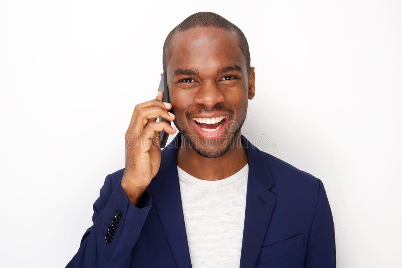 Fim acima do homem negro novo alegre que fala com o telefone celular pelo fundo branco foto de stock