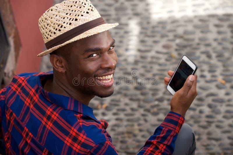 Fim acima do homem negro novo considerável com chapéu e telefone celular fotos de stock