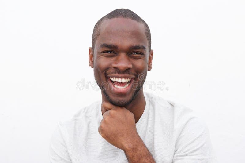 Fim acima do homem negro novo considerável que sorri com mão ao queixo contra a parede branca imagem de stock