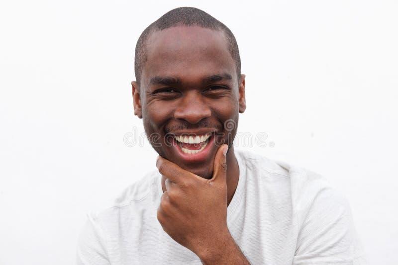 Fim acima do homem negro novo considerável que sorri com mão ao queixo fotografia de stock