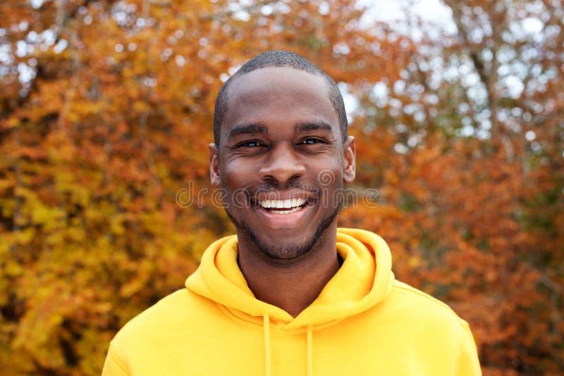Fim acima do homem negro novo considerável que sorri contra as folhas de outono no fundo fotografia de stock