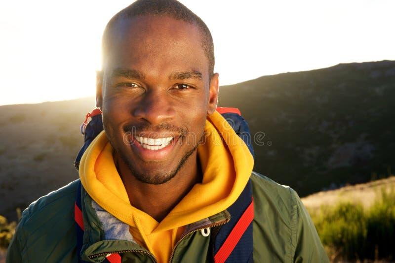 Fim acima do homem negro novo de sorriso que caminha nas montanhas com trouxa imagem de stock