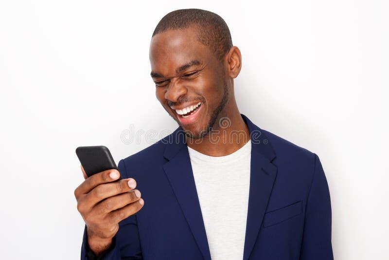 Fim acima do homem negro novo de sorriso que olha o telefone celular pela parede branca imagem de stock royalty free