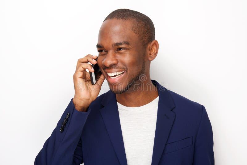 Fim acima do homem negro novo feliz que fala com o telefone esperto pelo fundo branco fotos de stock royalty free