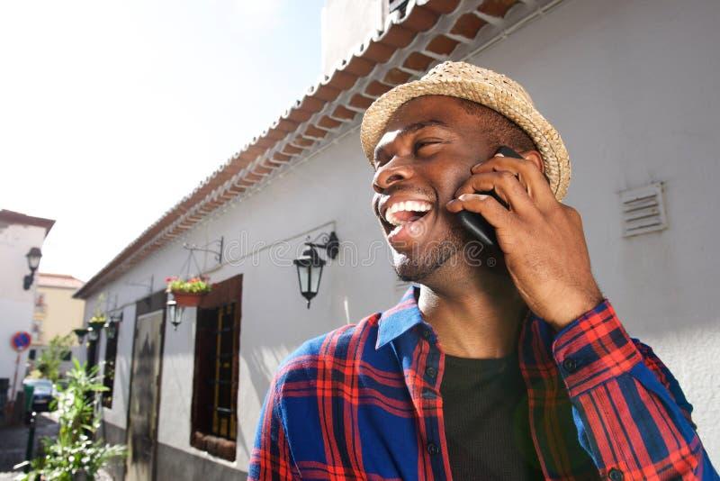 Fim acima do homem novo afro-americano feliz que fala com telefone celular fora imagem de stock royalty free