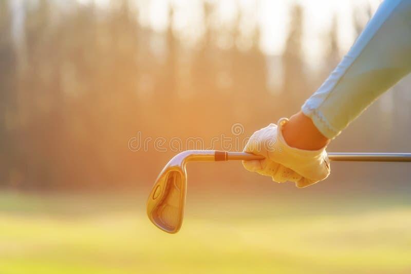 Fim acima do jogador de golfe da mão O golfe do jogador das mulheres que guarda clubes para aquece e relaxa o corpo antes do jogo imagens de stock royalty free
