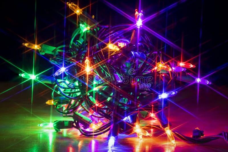 Fim acima do pacote de incandescência colorido de luzes de Natal imagem de stock