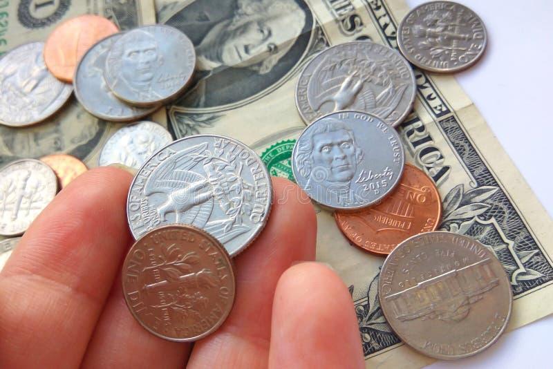 Fim acima do quarto americano, moedas da moeda de dez centavos à disposição foto de stock