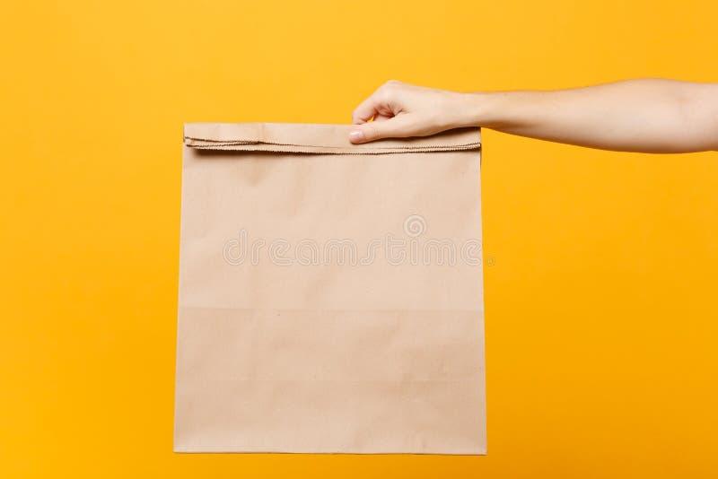 Fim acima do saco de papel vazio vazio claro marrom fêmea do ofício da posse à disposição para afastado isolado no fundo amarelo  foto de stock royalty free