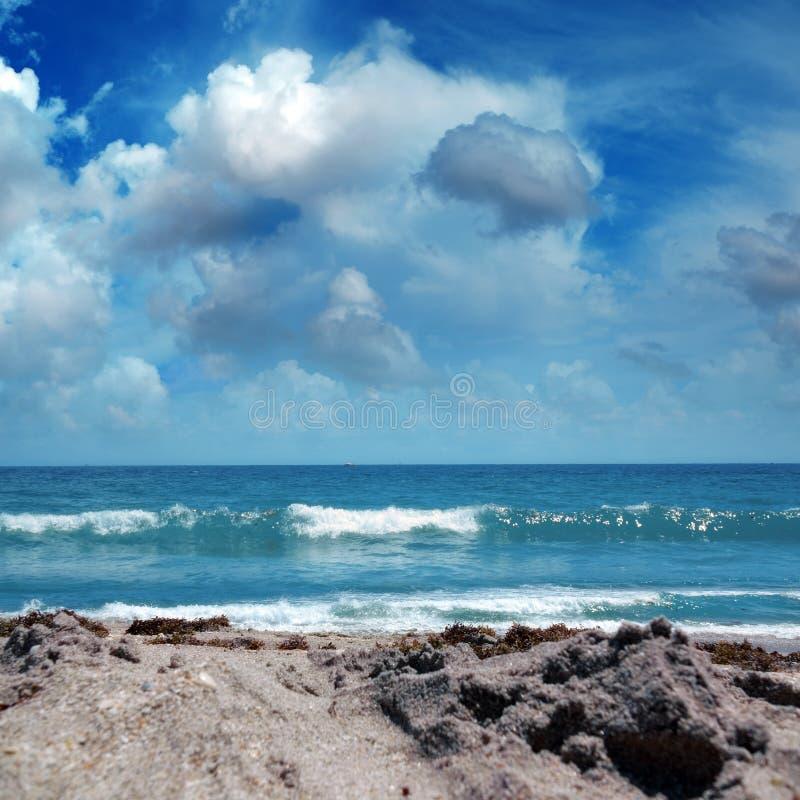 Fim acima do seascape com Sandy Beach e ondas no mar sobre nebuloso imagens de stock royalty free