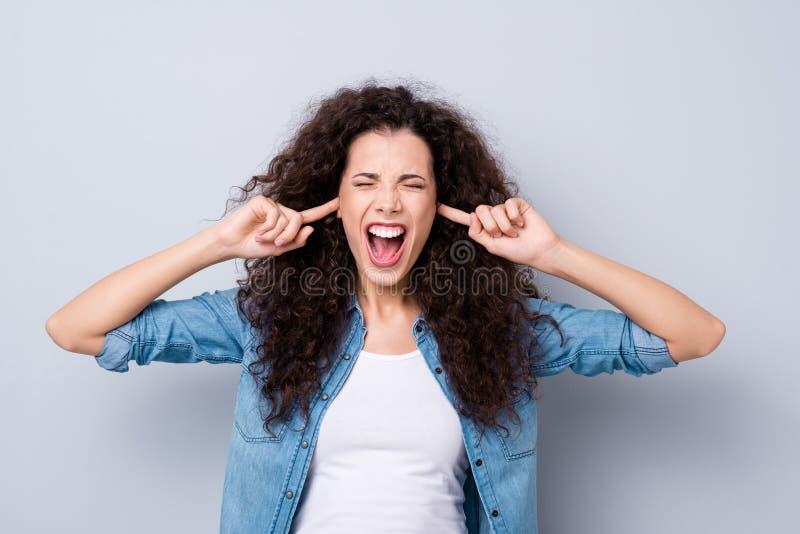 Fim acima do seu bonito surpreendente gritando da foto os braços da senhora fechados esconde a dor terrível das orelhas para não  imagem de stock