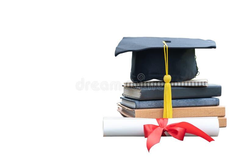 Fim acima do tampão da graduação e do papel pretos do certificado com fita vermelha em uma pilha de livros do vintage isolados imagem de stock