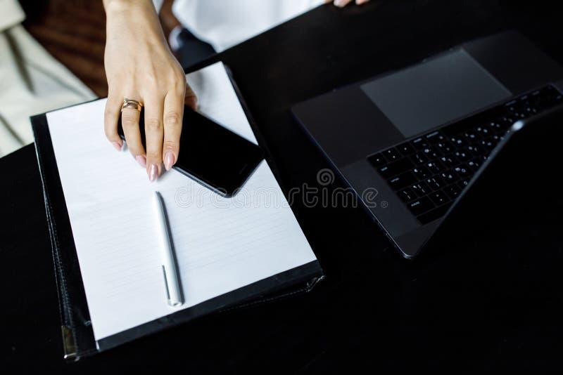 Fim acima do telefone celular da terra arrendada da mulher de negócios e do laptop da utilização na mesa do café Conceito de uma  foto de stock royalty free