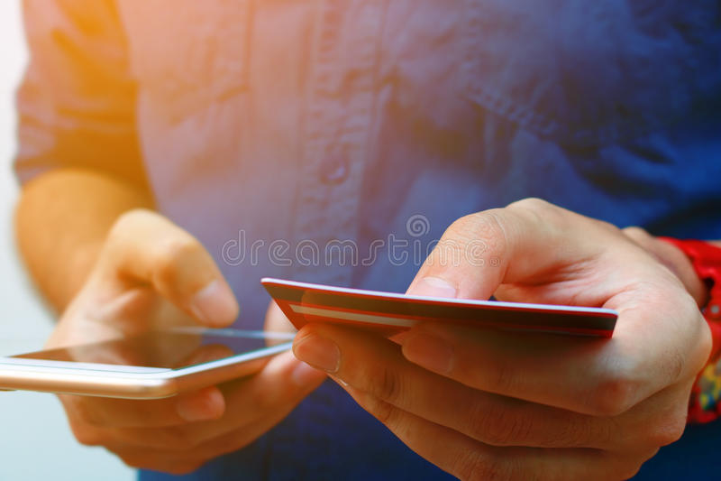 Fim acima do telefone esperto do uso do homem novo e de guardar o cartão de crédito, s fotografia de stock