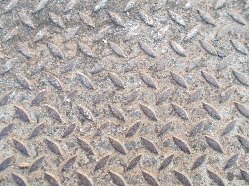 Fim acima do teste padrão de aço velho com o sujo do solo e da areia nos fundos da caminhada do trajeto imagens de stock