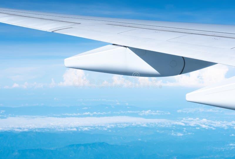 Fim acima do voo da asa do avião no céu azul no dia ensolarado sobre a nuvem imagem de stock