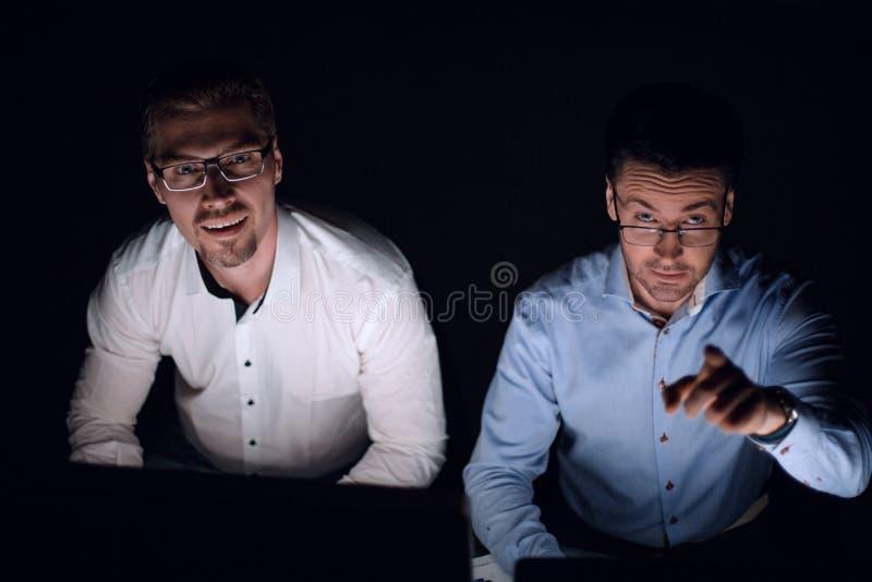 Fim acima dois colegas que trabalham em computadores imagens de stock royalty free