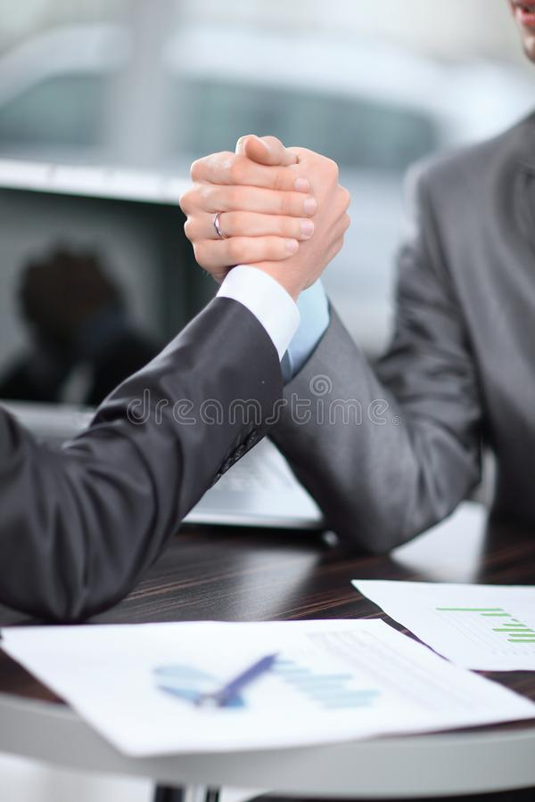 Fim acima dois homens de negócios são contratados na luta romana de braço em uma mesa foto de stock