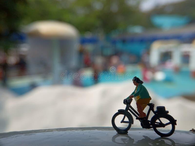 Fim acima dos brinquedos de Mini Figure Woman que bicycling na associação horizontal branca do parque da água com espaço negativo imagens de stock royalty free