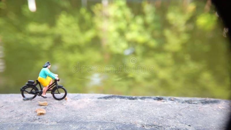 Fim acima dos brinquedos de Mini Figure Woman que bicycling na maneira do trajeto do lado do rio com espaço negativo ou da cópia  fotografia de stock royalty free