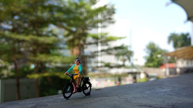 Fim acima dos brinquedos de Mini Figure Woman que bicycling na maneira do trajeto do lado do rio com espaço negativo ou da cópia  foto de stock royalty free
