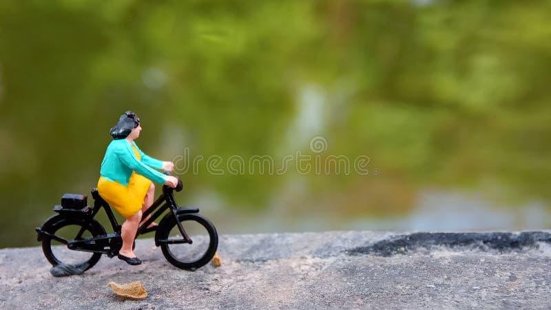 Fim acima dos brinquedos de Mini Figure Woman que bicycling na maneira do trajeto do lado do rio com espaço negativo ou da cópia  imagens de stock