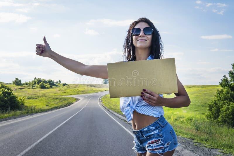 Fim acima dos cursos da menina que viajam com um sinal do cartão em suas mãos uma menina na estrada do short e dos saltos dos vid imagens de stock