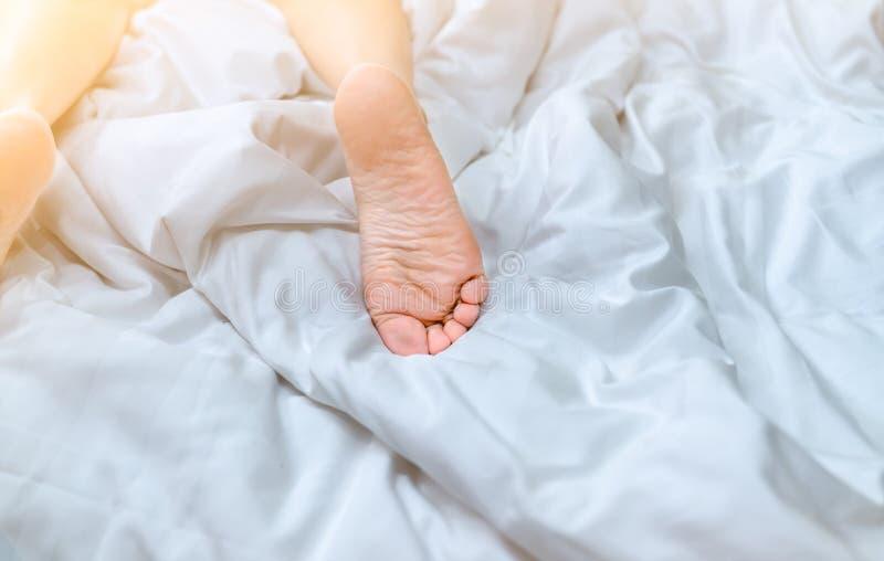 Fim acima dos pés desencapados da mulher na cama sobre a cobertura e a folha de cama brancas no quarto da casa ou do hotel Dormin fotos de stock royalty free