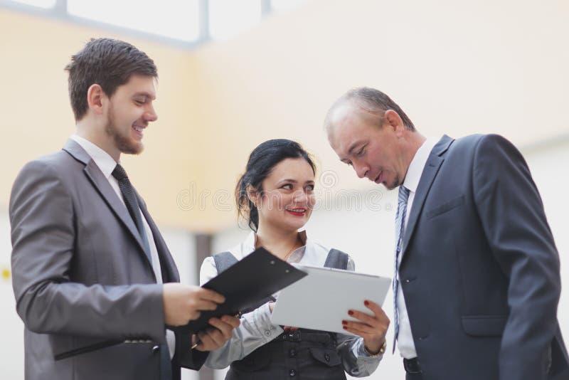 Fim acima empregados que olham a tela de uma tabuleta digital fotos de stock royalty free