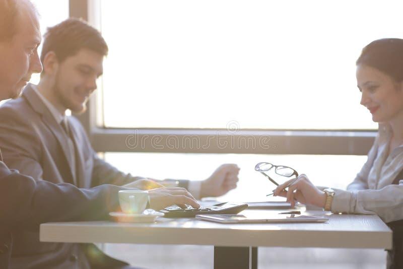 Fim acima a equipe do negócio considera o lucro usando a calculadora fotografia de stock royalty free