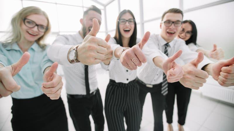 Fim acima Equipe feliz do negócio que mostra os polegares acima imagens de stock royalty free