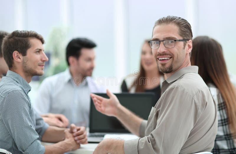 Fim acima homem de negócios bem sucedido que senta-se em sua mesa com uma equipe do negócio foto de stock royalty free