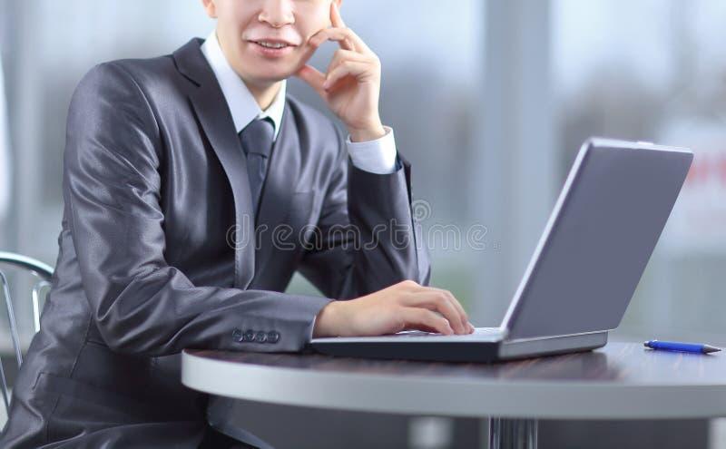 Fim acima homem de negócios de sorriso que senta-se na frente do portátil aberto imagem de stock royalty free