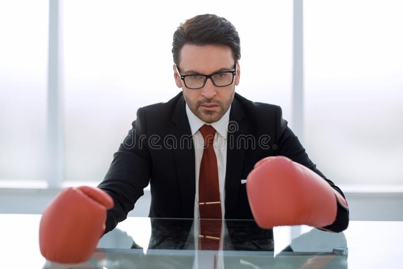 Fim acima luvas responsáveis de Boxing do homem de negócios que sentam-se na mesa fotos de stock