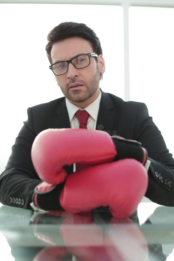 Fim acima luvas seguras de Boxing do homem de negócios que sentam-se em sua mesa foto de stock royalty free