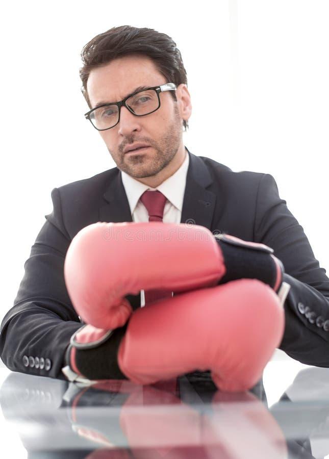 Fim acima luvas seguras de Boxing do homem de negócios que sentam-se em sua mesa fotografia de stock royalty free