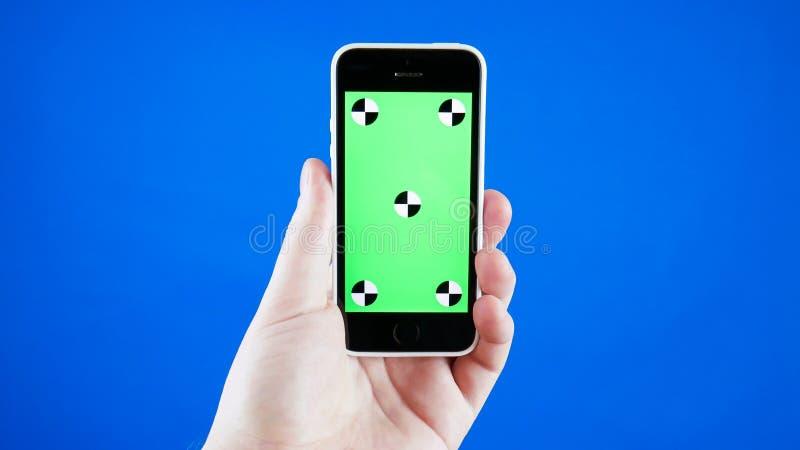 Fim acima A mão de um homem guarda um smartphone com uma tela verde r fotos de stock royalty free