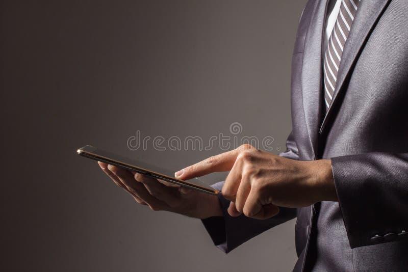 Fim acima Mão do homem de negócios na terra arrendada do terno e na aplicação cinzentas do toque foto de stock