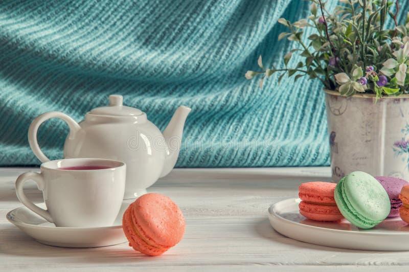 Fim acima Macarons coloridos do café da manhã de Provence em uma placa redonda, um copo do chá da baga, uma alfazema, um bule fotografia de stock