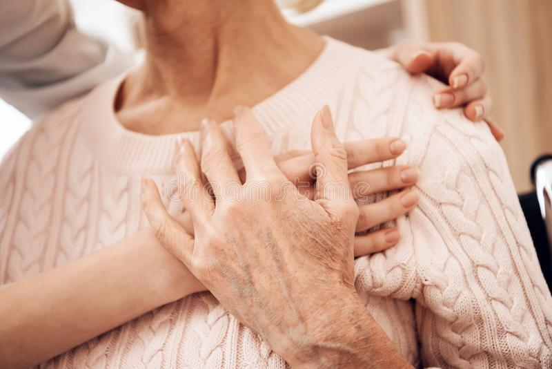 Fim acima A menina está importando-se com a mulher idosa em casa A menina está abraçando a mulher foto de stock royalty free