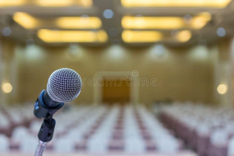 Fim acima Microfone na sala de conferências Microfone sobre a foto abstrata do borrão do fundo da sala de seminário imagem de stock