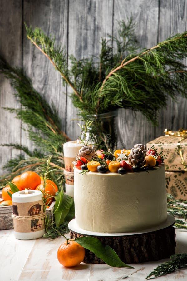 Fim acima O bolo de ano novo, mirtilos decorados, morangos, kumquat Estão próximo as tangerinas alaranjadas, queimando velas fest fotos de stock
