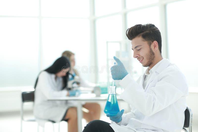 Fim acima o cientista novo faz a análise do líquido na garrafa fotografia de stock royalty free