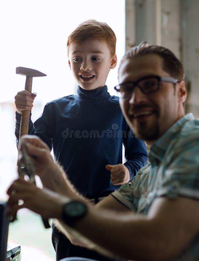 Fim acima o filho pequeno ajuda seu pai a fazer reparos imagem de stock royalty free