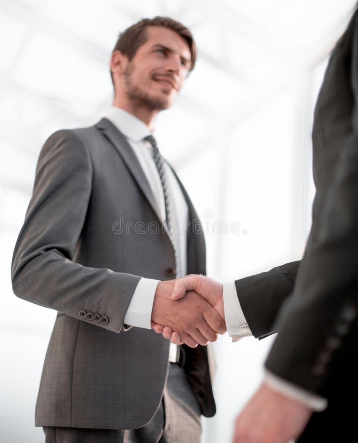 Fim acima o homem de negócios agita as mãos com seu sócio fotografia de stock
