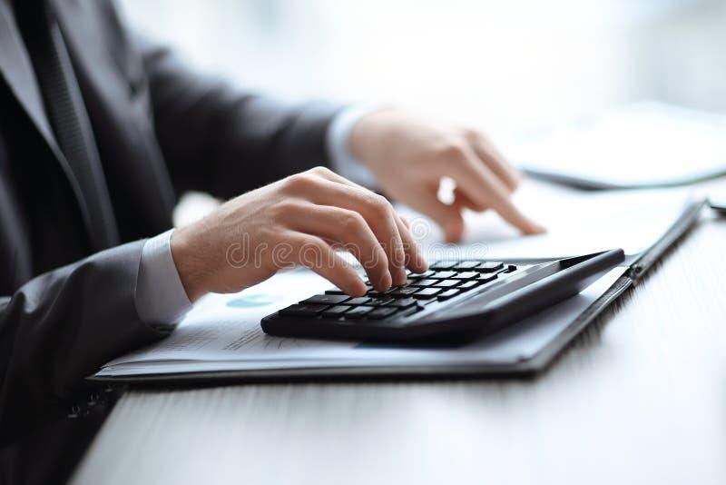 Fim acima o homem de neg?cios pode usar a calculadora para calcular o lucro fotografia de stock royalty free