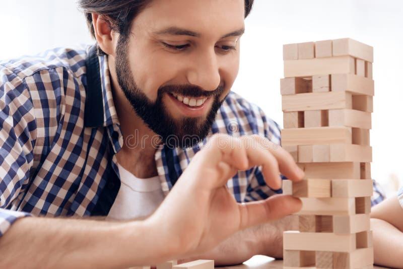 Fim acima O homem farpado de sorriso remove os blocos de madeira da torre foto de stock